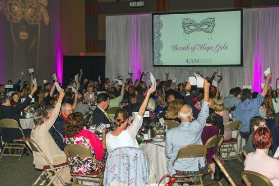 Raising bidding paddles at the Breath of Hope Gala.
